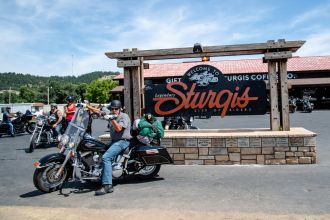 A biker poses for a photo in front of the Sturgis welcome sign during the 80th annual Sturgis Motorcycle Rally on Saturday, Aug. 15, 2020, in Sturgis, S.D. (Amy Harris)
