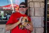 A biker poses for a photo with a dog during the 80th annual Sturgis Motorcycle Rally on Saturday, Aug. 15, 2020, in Sturgis, S.D. (Amy Harris)